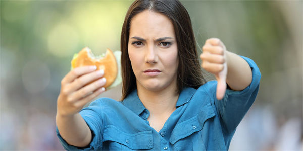 Woman holding a burger and giving a thumbs down