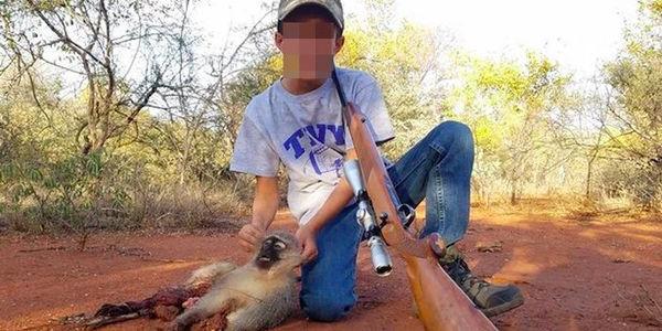 Boy posing next to murdered monkey